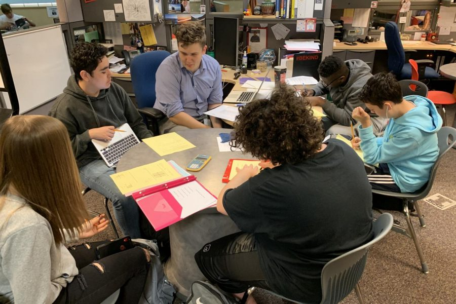 Math Instructor Steven Emmerich sits at his crowded desk and helps students during his open mods.