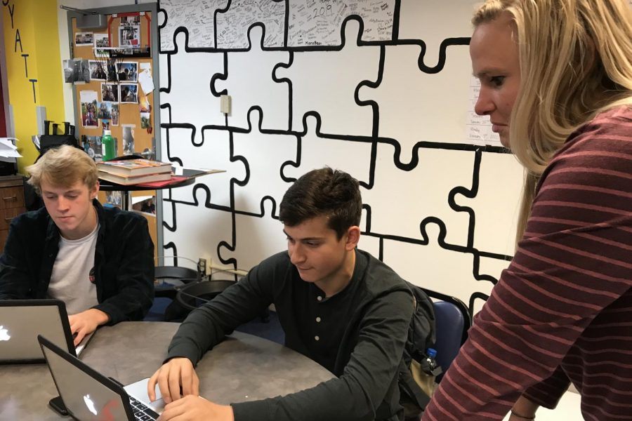 Marketing 2 students, seniors Spencer Schneiderman and Jackson Rall, discuss their project with Marketing 2 instructor Kalen Carlson.