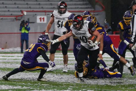 Junior Ben Radicia stiff arms a Bellevue West defender to get a first down.