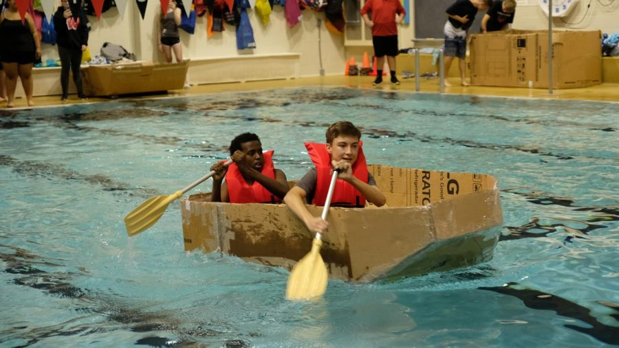 Engineering students test out their boat designs in the pool.
