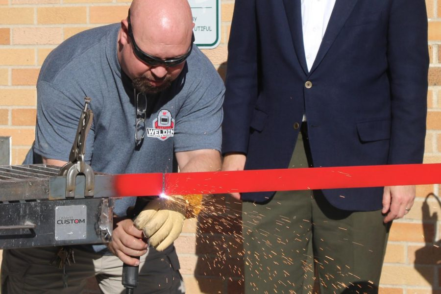 Engineering and Technology Instructor John Bombac participates in the ribbon welding ceremony to debut the welding lab expansion project.