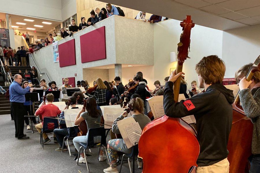 Orchestra members perform during the annual flash mob concert in the landing.