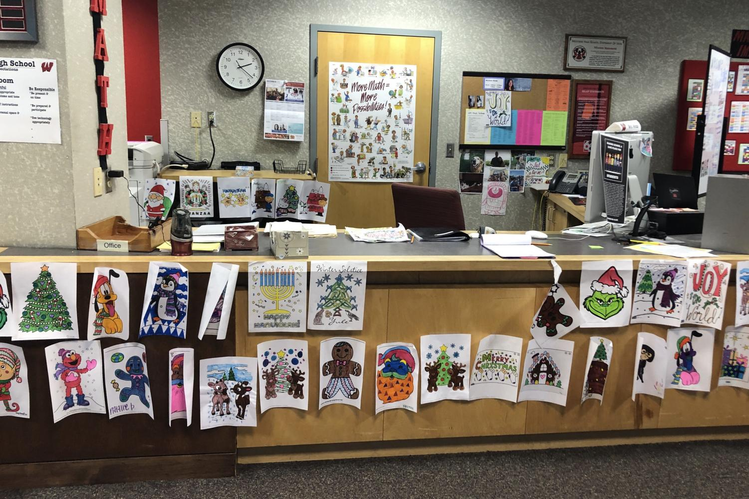 Educational Assistant Michelle Hinde showcases the students' artwork at her desk in the Math IMC.