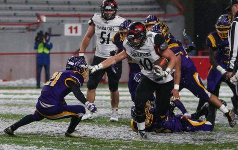 Junior Ben Radicia stiff arms a Bellevue West defender to get a first down.