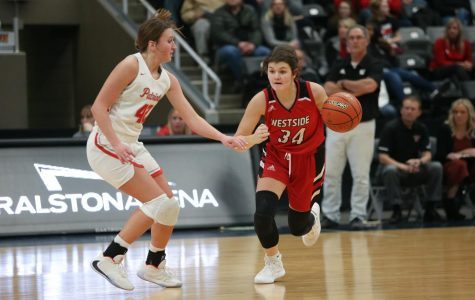 Westside senior Abby Hellman drives against Millard South's Maddie Krull in the Metro Holiday Tournament championship game.