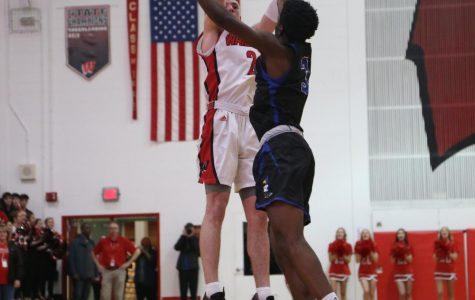 Westside senior Jadin Booth rises over Creighton Prep's Justin Sitti for one of his six made three pointers on Friday.
