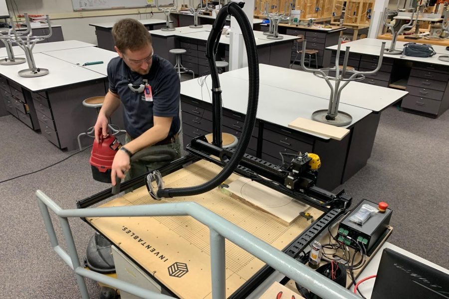 Engineering and Technology instructor Paul Cross tests out the new X-Carve machine the department recently purchased.
