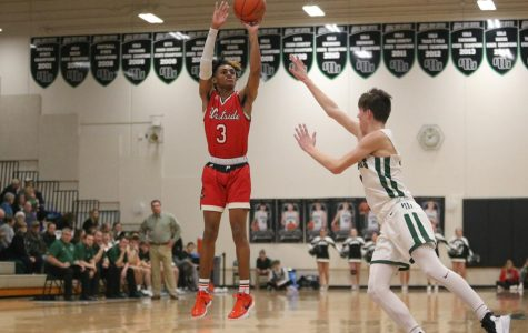 Senior, PJ Ngambi shooting the basketball while being guarded by Millard West's player.