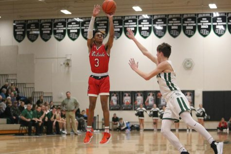 Senior, PJ Ngambi shooting the basketball while being guarded by Millard West