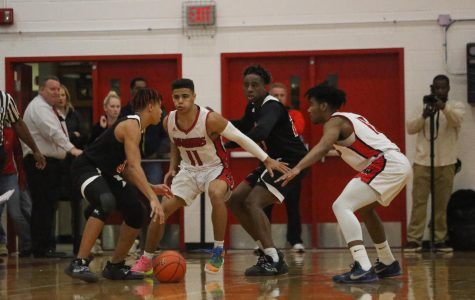 Sophomore, Reggie Thomas and Senior, Carl Brown both guarding Senior, Tyrece Griggs from Omaha South.