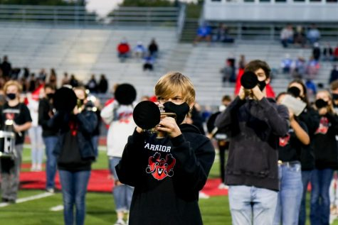 Westside marching band performs through specialized masks and bell-covers during the homecoming football game.