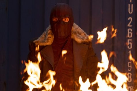 Zemo (Brühl) in his signature mask assisting Sam (Mackie), Bucky (Stan), and Sharon (VanCamp).