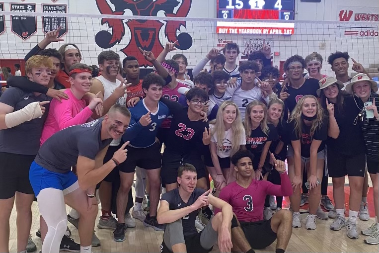 Seniors pose on the volleyball court after their victory over the junior team.