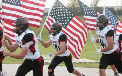 Kyle Vincentini brings out an American flag in their game up against Papillion-La Vista - Photo by Mary Nilius