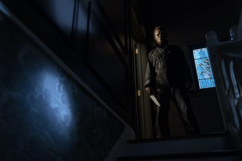 Michael Myers (Courtney) standing at the top of his stairs in his childhood home, looking down at Allyson (Matichak).